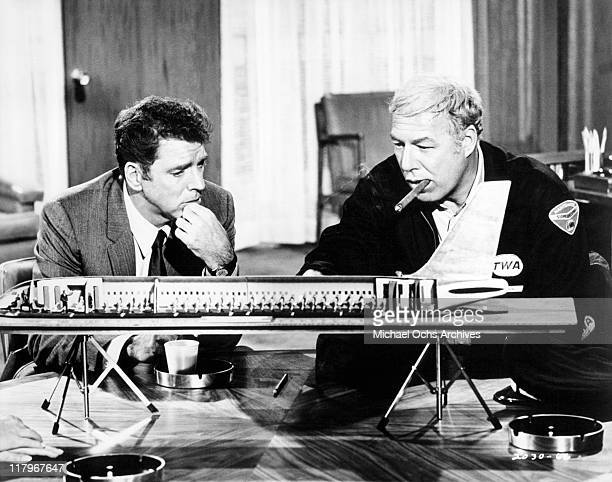 George Kennedy and Burt Lancaster looking at an airplane model in a scene from the film 'Airport' 1970