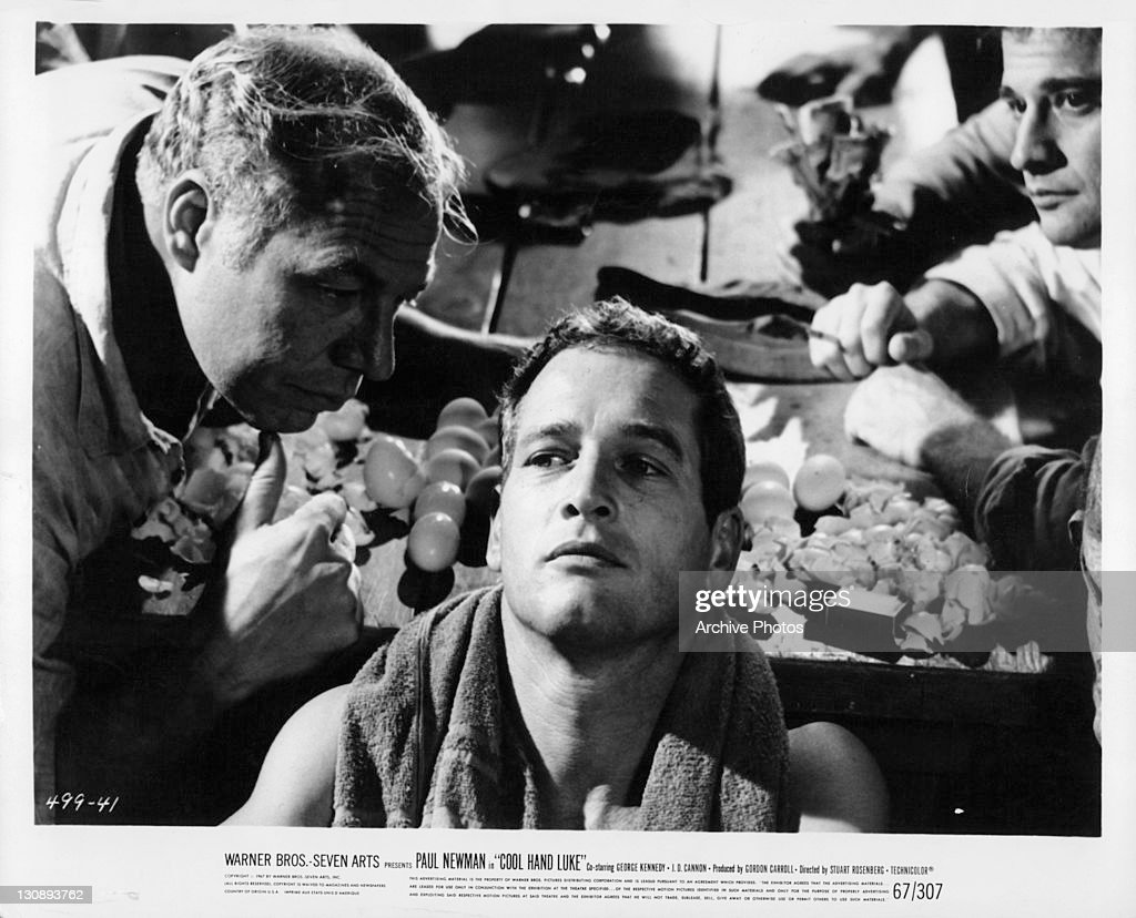 George Kennedy leaning into Paul Newman in a scene from the film 'Cool Hand Luke', 1967.