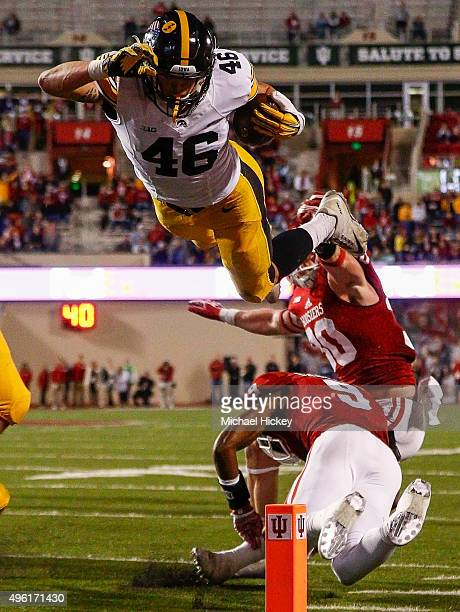 George Kittle of the Iowa Hawkeyes dives into the end zone for a touchdown over Jonathan Crawford of the Indiana Hoosiers at Memorial Stadium on...