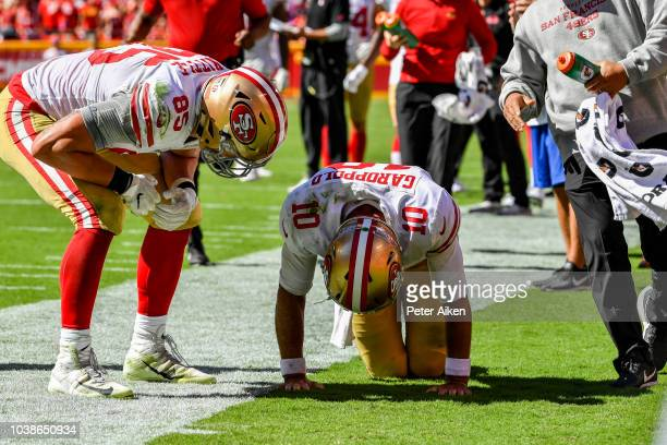 George Kittle of the San Francisco 49ers checks on injured teammate Jimmy Garoppolo after a play in the fourth quarter of the game against the Kansas...