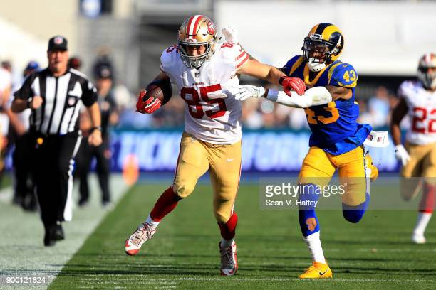 George Kittle of the San Francisco 49ers eludes John Johnson of the Los Angeles Rams on a pass play during the first half of a game at Los Angeles...
