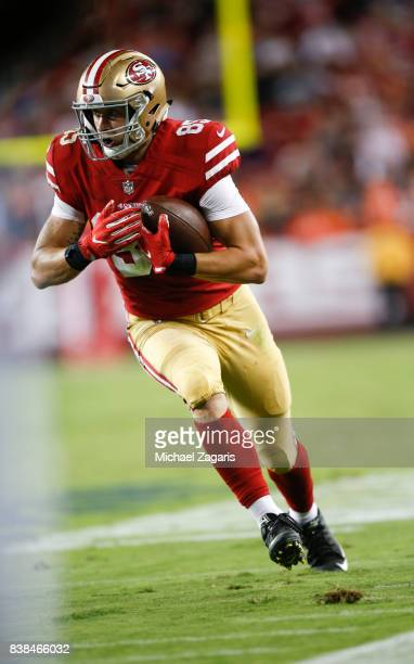 George Kittle of the San Francisco 49ers heads to the end zone on a touchdown pass during the game against the Denver Broncos at Levi Stadium on...