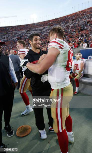 George Kittle of the San Francisco 49ers is congratulated by Jimmy Garoppolo on the sideline after breaking the NFL single season record for most...