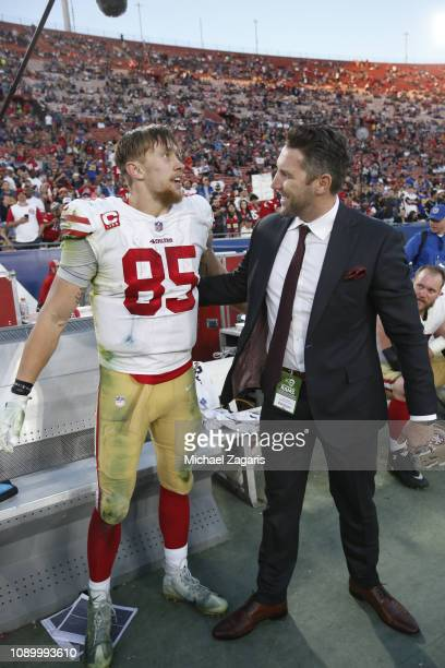 George Kittle of the San Francisco 49ers is congratulated by Vice President of Player Personnel Adam Peters on the sideline after breaking the NFL...