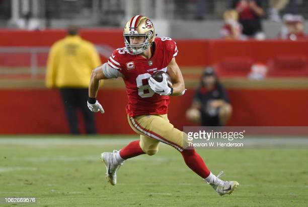 George Kittle of the San Francisco 49ers runs with the ball after catching a pass against the Oakland Raiders during the second half of their NFL...