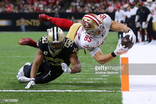 George Kittle of the San Francisco 49ers scores a touchdown as Craig Robertson of the New Orleans Saints defends during the second half of a game at...