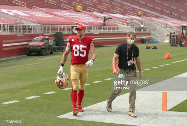 George Kittle of the San Francisco 49ers walks off the field with trainer Tim McAdams just before halftime of their game against the Arizona...