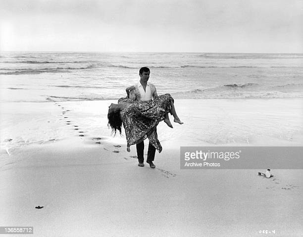 George Lazenby carries Diana Rigg out of the surf after halting her suicide attempt in a scene from the film 'On Her Majesty's Secret Service' 1969