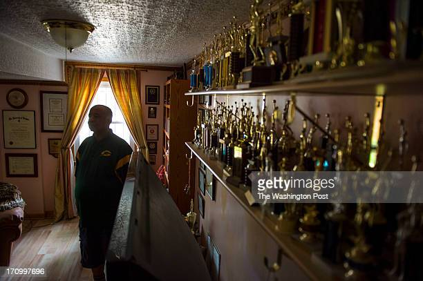 George Leftwich is photographed next to a trophy shelf at his home on June 18 2013 in Silver Spring Md Leftwich is retiring from Archbishop John...