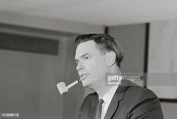 George Lincoln Rockwell American Nazi Party leader smokes a corn cob pipe as he listens to a question at press conference before he spoke at Lawrence...