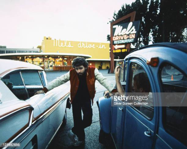 George Lucas US film director posing between two cars with 'Mel's Drivein' in the background on the set of 'American Graffiti' San Francisco...