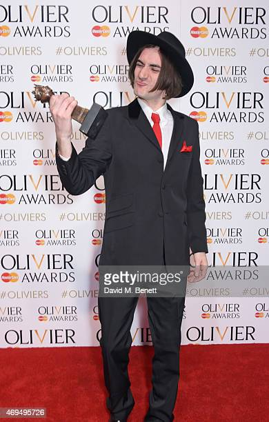 "George Maguire, winner of the Best Actor In A Supporting Role In A Musical for ""Sunny Afternoon"", poses in the winners room at The Olivier Awards at..."