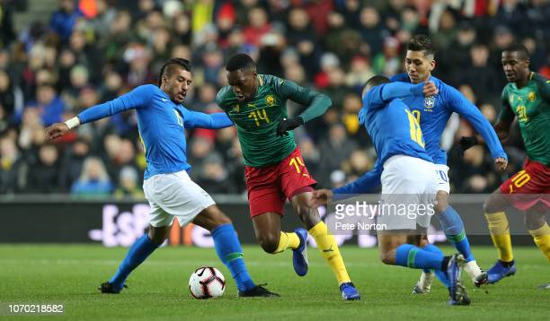 George Mandjeck of Cameroon moves with the ball past Paulinho and Alex Sandro of Brazil during the International Friendly match between Brazil and...