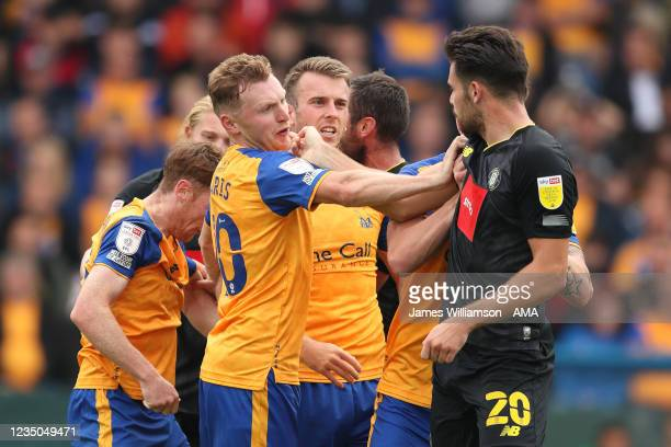 George Maris of Mansfield Town and Connor Hall of Harrogate Town clash during the Sky Bet League Two match between Mansfield Town and Harrogate Town...