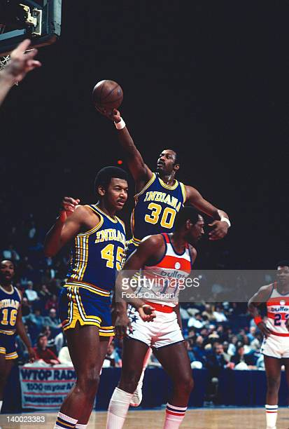 George McGinnis of the Indiana Pacers lays the ball up over Elvin Hayes of the Washington Bullets during an NBA basketball game circa 1981 at the...