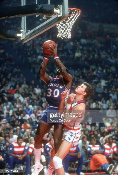 George McGinnis of the Philadelphia 76ers goes up to shoot over Mitch Kupchak of the Washington Bullets during an NBA basketball game circa 1977 at...