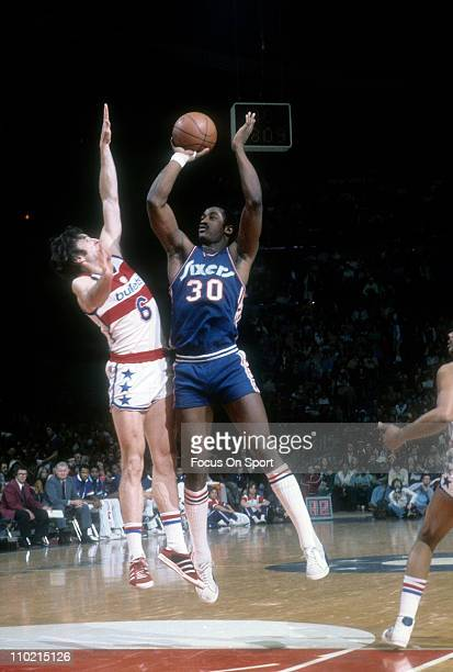 George McGinnis of the Philadelphia 76ers shoots over Mike Riordan of the Washington Bullets during an NBA basketball game circa 1978 at the...