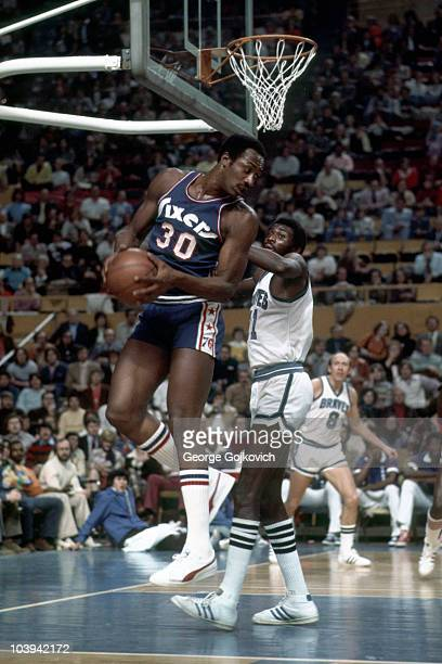 George McGinnis of the Philadelphia Sixers rebounds against Bob McAdoo of the Buffalo Braves as Bob Weiss looks on during a National Basketball...