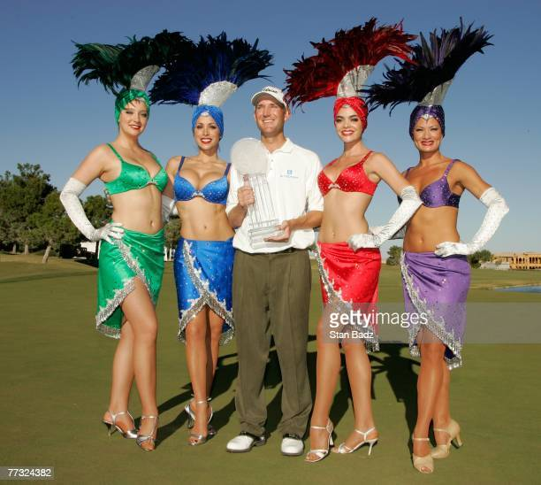 George McNeill holds the winner's trophy with Las Vegas showgirls after the fourth round of the Fryscom Open benefiting Shriners Hospitals for...