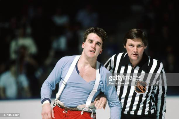George McPhee of the New York Rangers is escorted to the penalty box by a linesman after an altercation during an NHL game against the New York...
