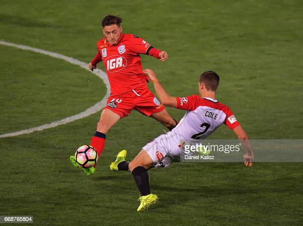 George Mells of United competes for the ball with Shannon Cole of the Wanderers during the round 27 ALeague match between Adelaide United and the...