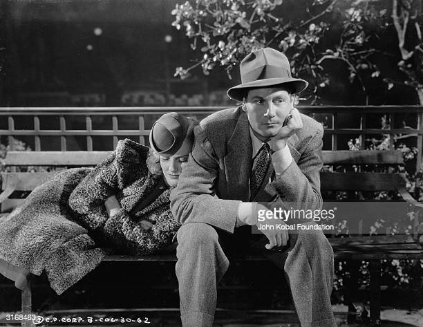 George Melville played by Joel McCrea looks troubled while Claire Peyton played by Jean Arthur sleeps beside him on a park bench in a scene from...