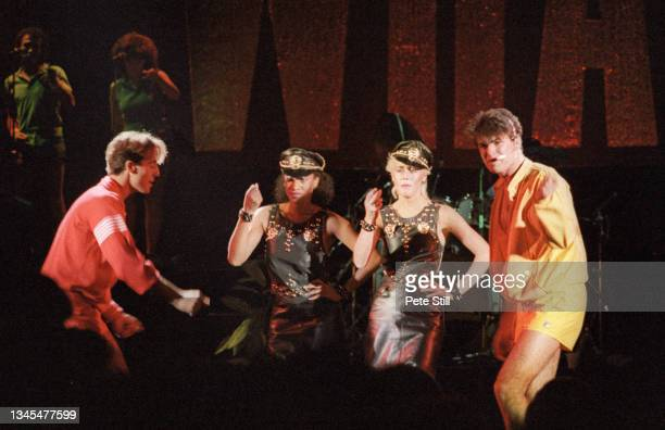 George Michael and Andrew Ridgeley of English pop duo Wham with backing singers Helen DeMacque and Shirlie Holliman perform on stage at Hammersmith...