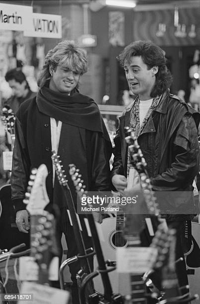 George Michael and Andrew Ridgeley of Wham looking at a display of guitars for sale during the pop duo's 1985 world tour January 1985 'The Big Tour'...