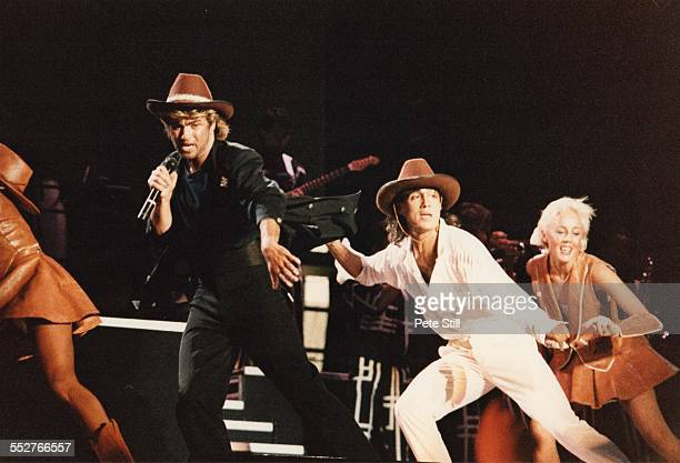 George Michael and Andrew Ridgeley of Wham perform on stage with Shirlie Holliman of Pepsi and Shirlie at the National Exhibition Centre on February...