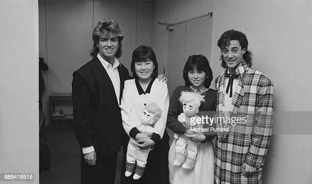George Michael and Andrew Ridgeley of Wham with two teenage fans each carrying a Wham doll during the pop duo's 1985 world tour January 1985 'The Big...