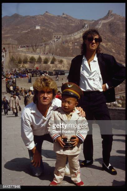 George Michael and Andrew Ridgley members of the rock group Wham stand with a small boy at the Great Wall of China Wham was the first popular western...