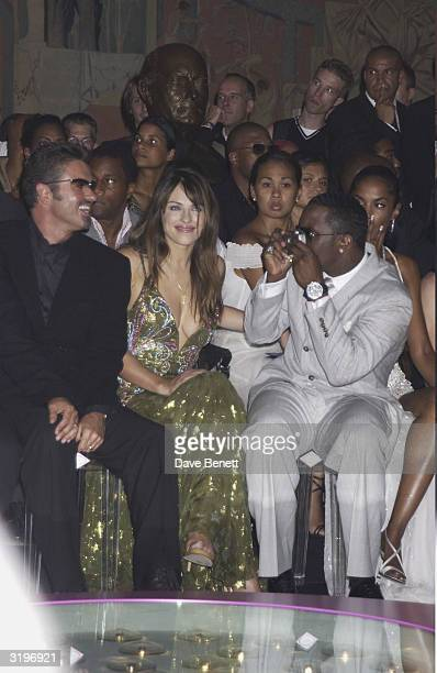 George Michael and Elizabeth Hurley are filmed by Sean Combs in the audience for a Versace show at the Theatre National de Chaillot at the Trocadero...
