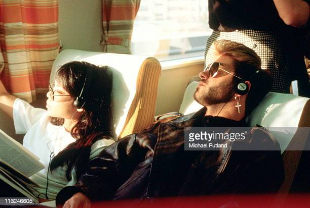George Michael with girlfriend Kathy Yeung, on a train listening to a Walkman, Japan, March 1988.