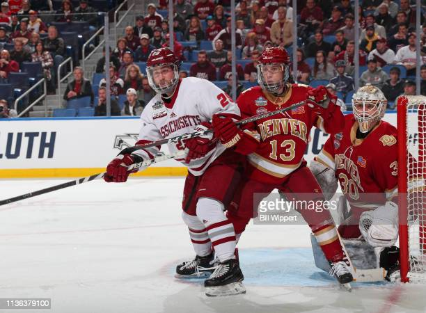 George Mika of the Massachusetts Minutemen is defended by Liam Finlay and Filip Larsson of the Denver Pioneers during the Division I Men's Ice Hockey...