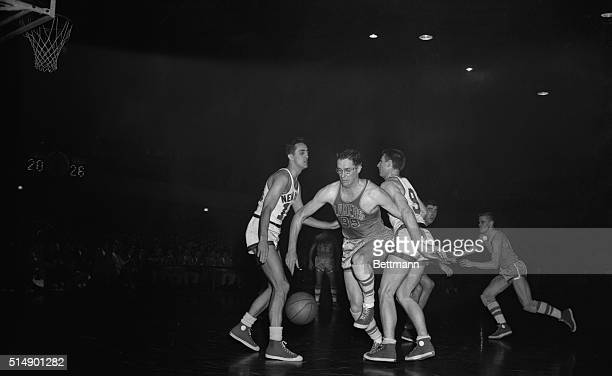 George Mikan of the Minneapolis Lakers is shown coming through center of Connie Simmoms New York Knickerbockers left and Ernie Vandeweghe Knicks...