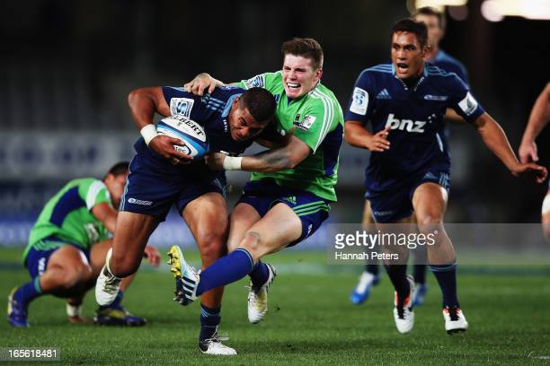 George Moala of the Blues fends off Colin Slade of the Highlanders during the round eight Super Rugby match between the Blues and the Highlanders at...