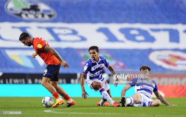 George Moncur of Luton Town runs past the challenges of Tennai Watson and Tom Holmes of Reading FC during the Carabao Cup Second Round match between...