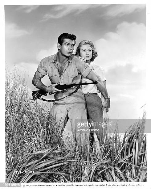 George Nader guards Virginia Mayo in a scene from the film 'Congo Crossing' 1956