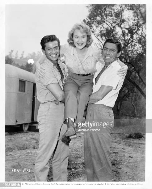 George Nader holds up Virginia Mayo with Michael Pate on set of the film 'Congo Crossing' 1956