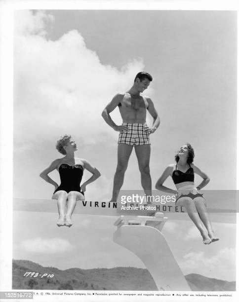 George Nader looking down at women on diving on board in publicity portrait the film 'Four Girls In Town' 1957