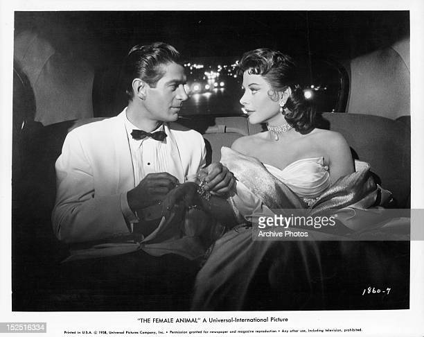 George Nader putting bracelet on Hedy Lamarr in the car in a scene from the film 'The Female Animal' 1958