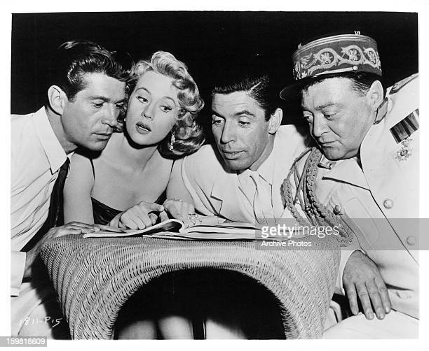George Nader Virginia Mayo Michael Pate and Peter Lorre flip through the script on set of the film 'Congo Crossing' 1956