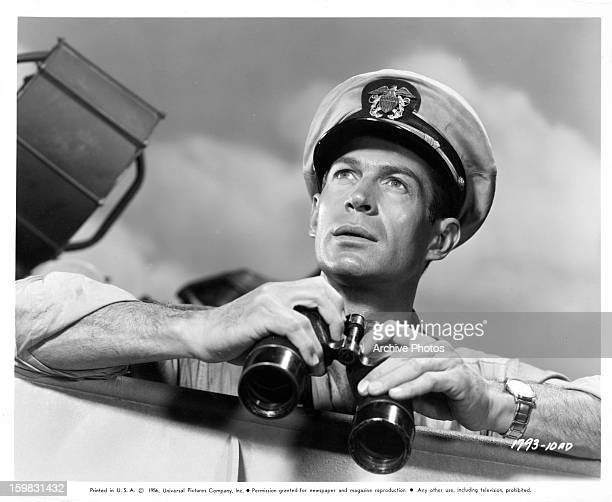 George Nader with binoculars in publicity portrait for the film 'Away All Boats' 1956