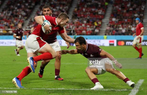 George North of Wales charges through the tackle of Guram Gogichashvili and Soso Matiashvili of Georgia as he goes on to score his sides sixth try...