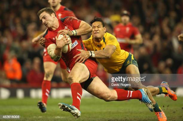 George North of Wales dives over for a try despite being held by Israel Folau during the international match between Wales and Australia at the...