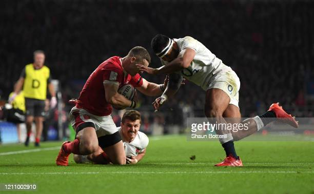 George North of Wales is tackled by Henry Slade of England and Manu Tuilagi of England which later resulted in a red card for Manu Tuilagi during the...