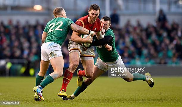 George North of Wales is tackled by Ian Madigan and Robbie Henshaw of Ireland during the RBS Six Nations match between Ireland and Wales at the Aviva...