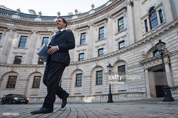 George Osborne UK chancellor of the exchequer carries a copy of his Autumn budget statement as he leaves the HM Treasury building before heading to...