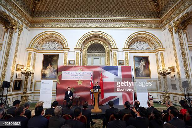 George Osborne UK chancellor of the exchequer center left sits on a stage and listens as Li Keqiang China's premier center speaks during the UK China...