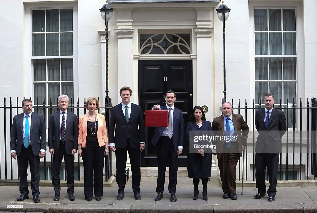 George Osborne, U.K. chancellor of the exchequer, centre, stands with the H.M. Treasury team, left to right, Gareth Johnson, parliamentary private secretary to David Gauke, Paul Deighton, U.K. commercial secretary to the treasury, Andrea Leadsom, U.K. economic secretary to the treasury, Danny Alexander, U.K. chief secretary to the treasury, Priti Patel, U.K. exchequer secretary to the treasury, Robert Halfon, parliamentary private secretary to George Osborne, and David Gauke, U.K. financial secretary to the treasury, outside 11 Downing Street in London, U.K., on Wednesday, March 18, 2015. U.K. unemployment fell to its lowest level in more than six years and real pay growth accelerated in a boost for Osborne as he prepares to announce his final budget before the election. Photographer: Chris Ratcliffe/Bloomberg via Getty Images